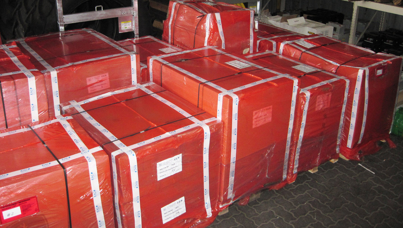 Airfreight consignment of automotive parts: Heavy cardboards on pallets, shrink-wrapped with resistant red RAC-Germany plastic film.